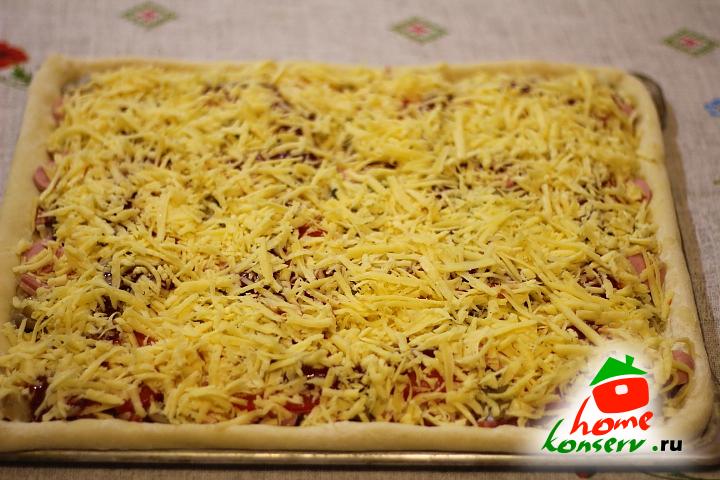 Посыпать натертым сыром пиццу